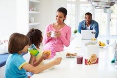 Семья имея завтрак в кухне совместно Стоковые Изображения