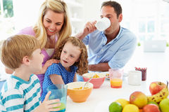 Семья имея завтрак в кухне совместно Стоковые Изображения RF