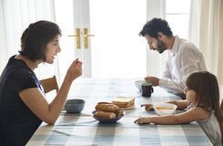 Семья имея завтрак совместно на обеденном столе Стоковые Изображения
