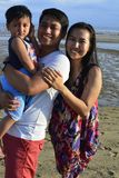 Семья имея потеху представляя для изображения на пляже с белым песком на малой воде Стоковые Изображения RF
