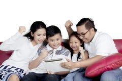 Семья используя цифровую таблетку на софе Стоковая Фотография RF