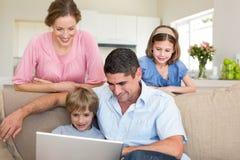Семья используя компьтер-книжку Стоковое фото RF