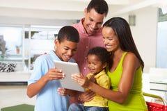 Семья используя таблетку цифров в кухне совместно стоковое изображение