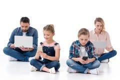 Семья используя smartphones, цифровую таблетку и компьтер-книжку Стоковая Фотография RF