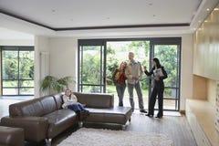 Семья и агент по продаже недвижимости наблюдающ новым свойством Стоковое фото RF