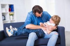 Семья и концепция влюбленности - молодой отец щекоча его маленький сына стоковые изображения rf