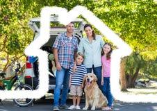 Семья и собака стоя на дороге против плана дома в предпосылке Стоковая Фотография
