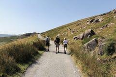 Семья идя вдоль следа к Snowdon, Уэльсу стоковые изображения