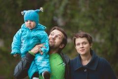Семья идя в парк осени - папа держа руки сыновьей стоковые изображения