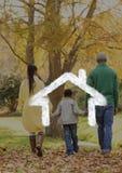 Семья идя в древесины против плана дома в предпосылке Стоковое фото RF
