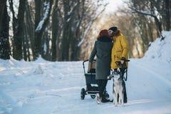 Семья идя с прогулочной коляской в зиме Стоковое фото RF