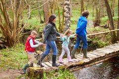 Семья идя через деревянный мост над потоком в лесе стоковые изображения rf