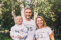 Семья конца-вверх счастливая в идентичных футболках с номерами и надписями - командой семьи, мамой, папой - обнимая в парке стоковые фотографии rf