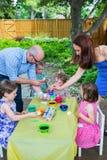 Семья красит пасхальные яйца снаружи Стоковое Фото