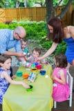 Семья крася и крася пасхальные яйца совместно Стоковое Изображение RF