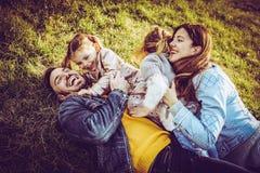 Семья лежа и играя на траве Стоковые Фото