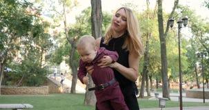 Семья, мама имея потеху играет с младенцем на деревьях зеленого цвета предпосылки на природе, радостных остатках видеоматериал