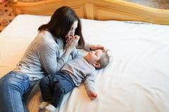 Семья, материнство, воспитание, люди и концепция ухода за детьми - счастливая мать целуя прелестного младенца в спальне стоковое изображение rf