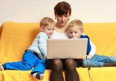 Семья. Мать и сыновьья используя компьтер-книжку дома Стоковое Фото