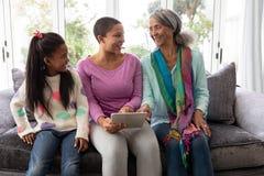 семья Мульти-поколения используя цифровой планшет на софе в живя комнате стоковые фотографии rf