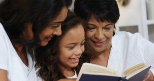 семья Мульти-поколения читая книгу в спальне 4k акции видеоматериалы