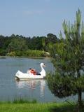 Семья наслаждаясь шлюпкой педали лебедя на парке сафари Woburn, Великобритании Стоковые Фото