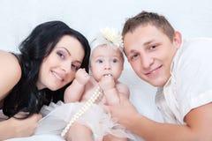 Семья на белой кровати в спальне Стоковая Фотография