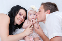 Семья на белой кровати в спальне Стоковое Изображение RF