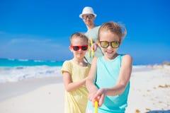 Семья на белом тропическом пляже имеет много потеху Отец и дети наслаждаются праздниками на seashore Стоковое Изображение