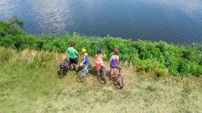 Семья на велосипедах задействуя outdoors, активных родителях и детях на велосипедах, виде с воздуха счастливой семьи при дети осл стоковая фотография
