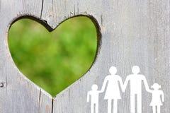 Семья на деревянной предпосылке с зеленым сердцем Стоковое Изображение RF