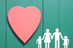 Семья на деревянной предпосылке с красным сердцем Стоковые Фото