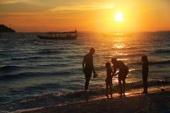 Семья на пляже на заходе солнца Стоковое фото RF