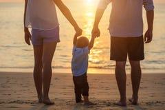 Семья на пляже, мать держа руку ее сына и идти, стоковые фото