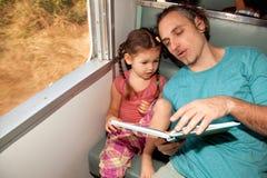Семья на поезде читая книгу Стоковые Изображения RF