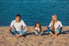 Семья на пляже Позиция лотоса Джинсыы стоковые изображения rf