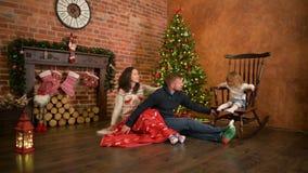 Семья на Рожденственской ночи на камине Родители и маленький ребенок раскрывая настоящие моменты Xmas Дети с подарочными коробкам сток-видео