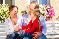 Семья на стенде сада перед домом Стоковые Фотографии RF