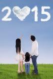 Семья на луге под 2015 Стоковое Изображение