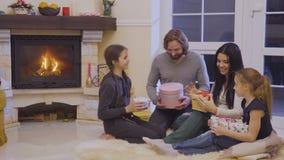 Семья обменивает подарки рождества в рождестве выравниваясь около камина видеоматериал