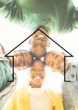Семья обнимая один другого против плана дома в предпосылке Стоковые Изображения RF