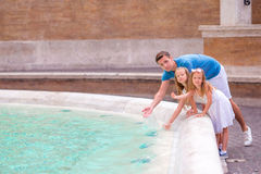Семья около фонтана Trevi в Риме Счастливые дети и папа наслаждаются их европейскими каникулами в Италии Стоковая Фотография RF