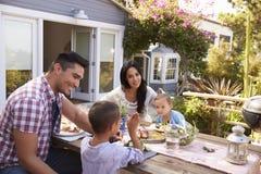 Семья дома есть внешнюю еду в саде совместно Стоковые Фото