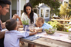 Семья дома есть внешнюю еду в саде совместно Стоковое Фото