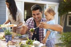 Семья дома есть внешнюю еду в саде совместно Стоковая Фотография RF
