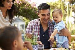 Семья дома есть внешнюю еду в саде совместно Стоковая Фотография