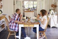 Семья дома есть еду в кухне совместно Стоковая Фотография