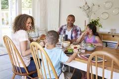 Семья дома есть еду в кухне совместно Стоковые Изображения