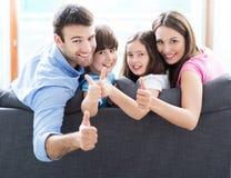 Семья дома с большими пальцами руки вверх стоковая фотография