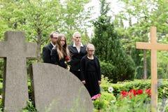 Семья оплакивая на могиле на кладбище Стоковая Фотография RF